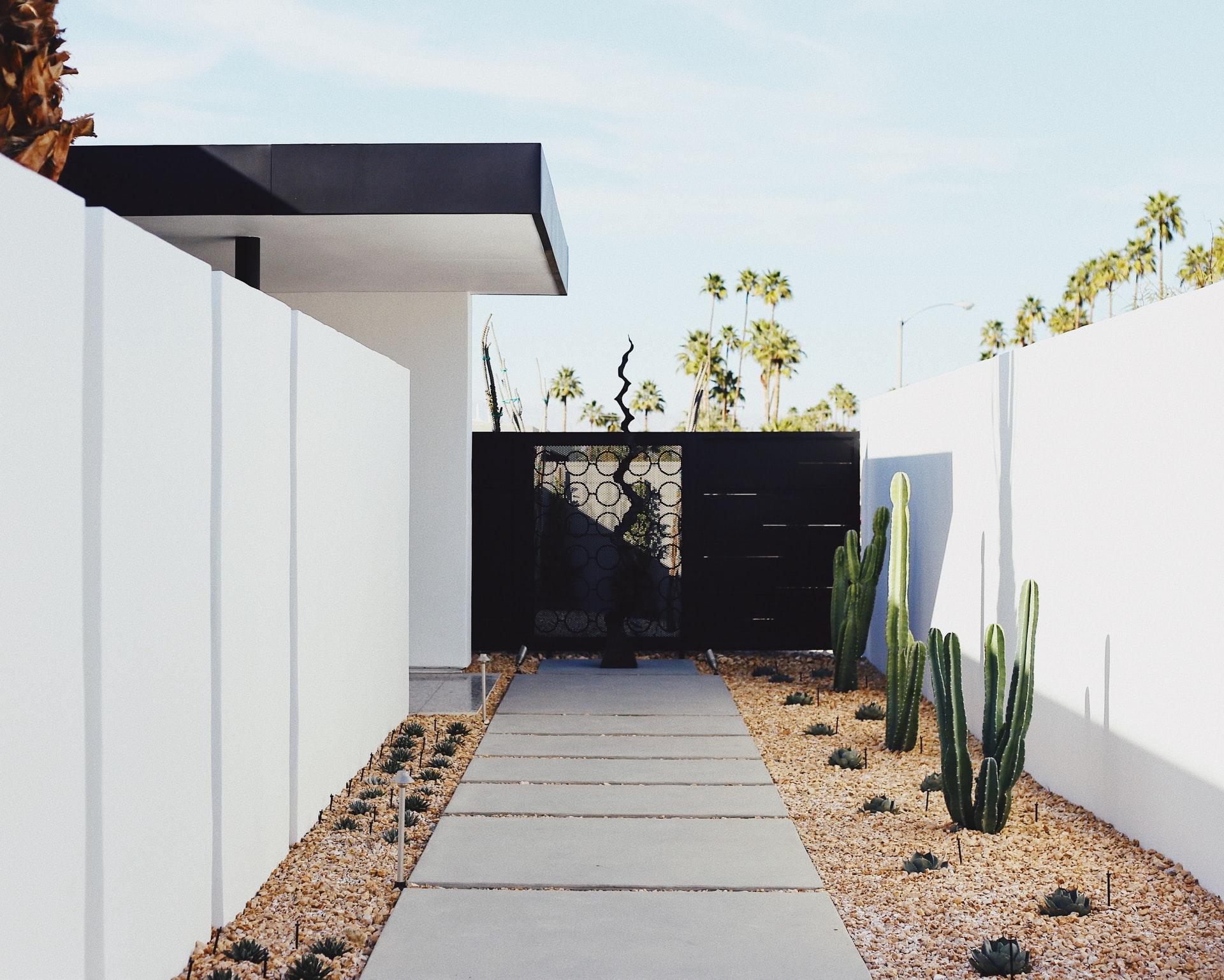 maison blanche avec marche jusqu'au portail avec cactus