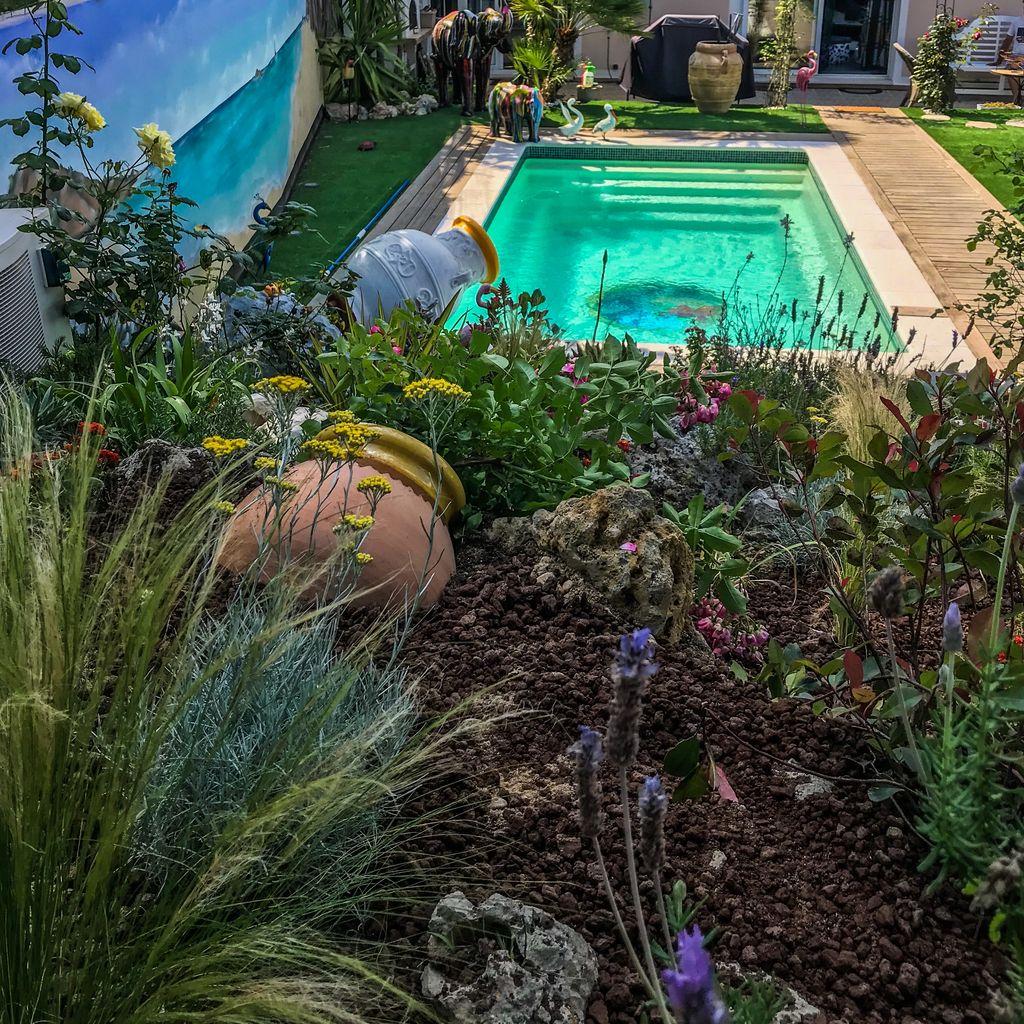 jardin avec piscine en fond et une jarre